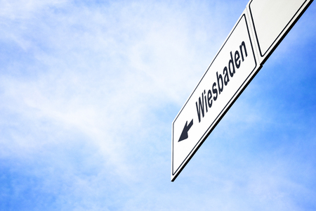White signboard with an arrow pointing left towards Wiesbaden, Hesse, Germany, against a hazy blue sky in a concept of travel, navigation and direction. Path included for the signboard