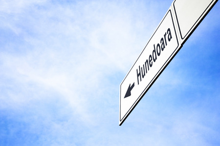 White signboard with an arrow pointing left towards Hunedoara, Romania, against a hazy blue sky in a concept of travel, navigation and direction. Path included for the signboard