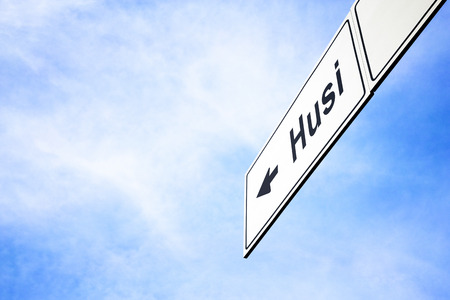 White signboard with an arrow pointing left towards Husi, Romania, against a hazy blue sky in a concept of travel, navigation and direction. Path included for the signboard