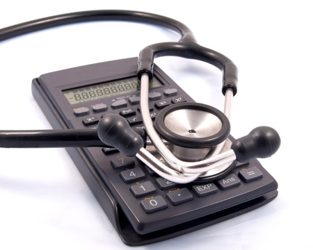 budgets: Stephascope placed over a calculator used by Doctors managing budgets Stock Photo