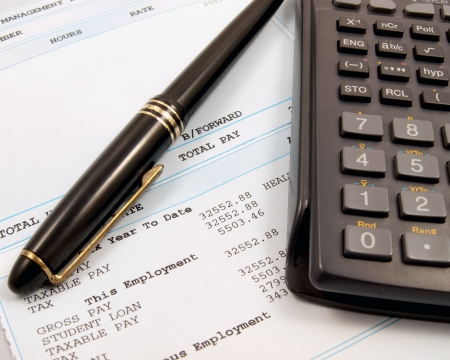 A payslip and pen with a calculator to work out finances