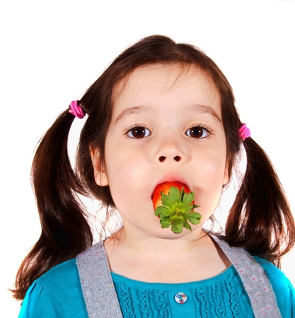 Young girl with fruit stuffed into mouth