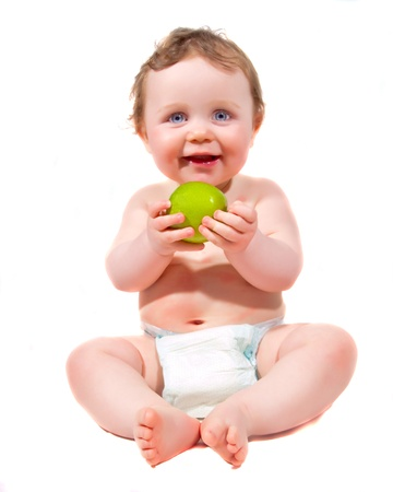 young baby holding an apple in front of him on a white background