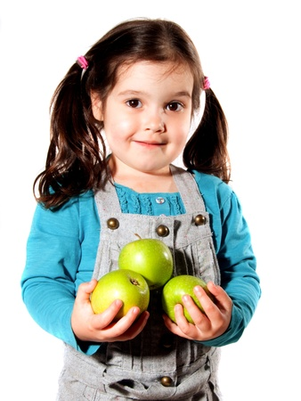 Young girl with black hair carrying three green apples