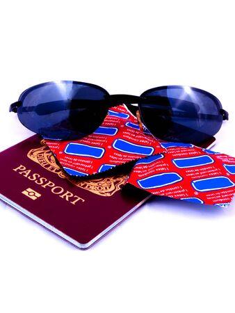 condones: Un pasaporte con gafas de sol y preservativos