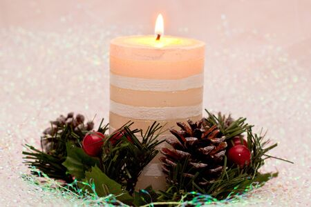 A lit candle for christmas surrounded by a holly ring