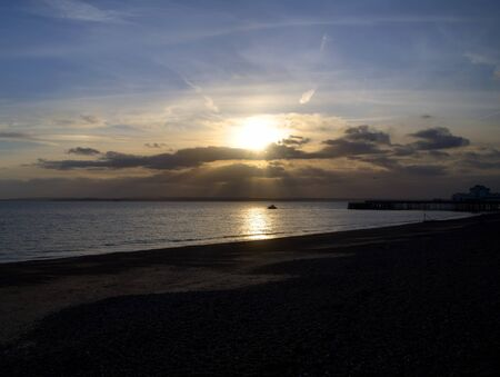 Sunsetting behind the clouds over the sea with a pier in view