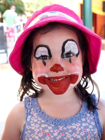 young girl with face painted as a clown
