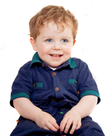 young boy in front of a white background smiling