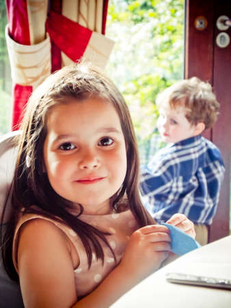 Little girl at a restaurant with boy in background