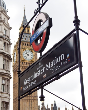 Westminster station sign with Westminster palace, London, Uk, June 2012