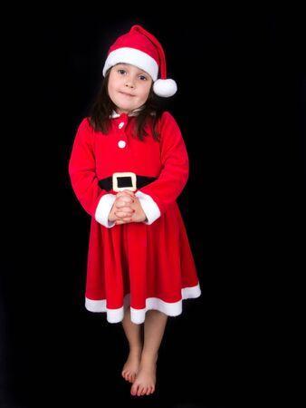 A little girl wearing a santa costume