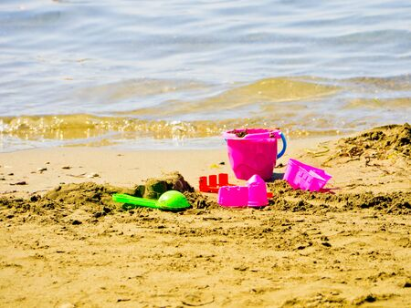 a pink bucket and spade on the beach