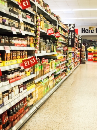 Shelving within a supermarket with signs highlighting discounts Editorial
