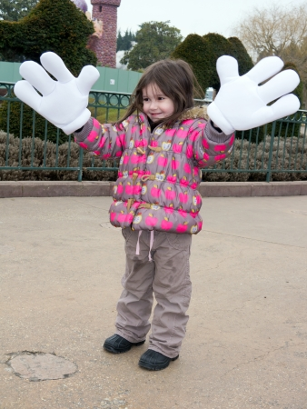 Little girl at disneyland with large Mickey Mouse gloves