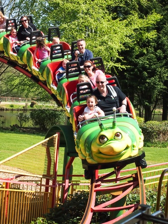 theme parks: people riding on a caterpillar rollercoaster Editorial