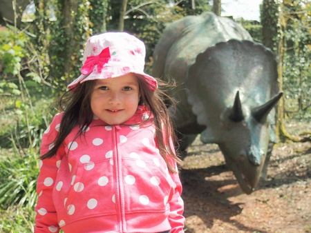 Little girl with a dinosaur behind her