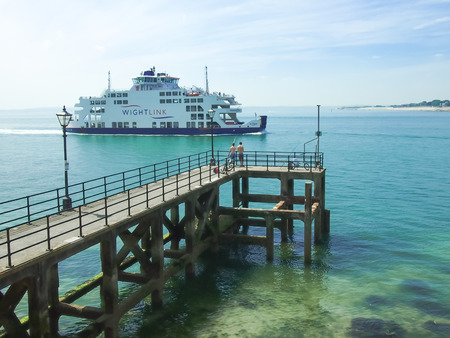 Wightlink ferry passes a fishing pier at the entrance to portsmouth harbour