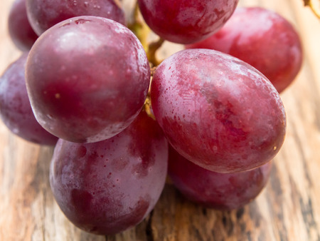 Purple grapes on a wooden surface