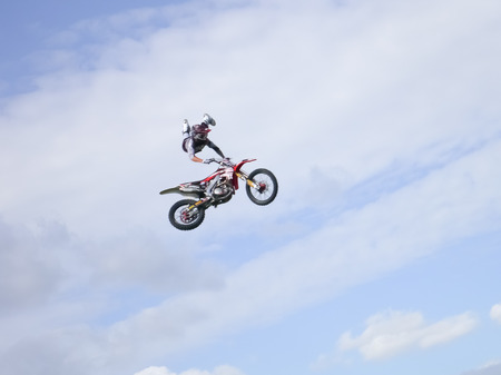 FMX rider against a blue sky with clouds