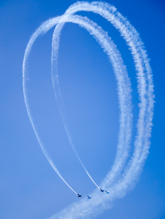 two aircraft complete a loop trailing smoke