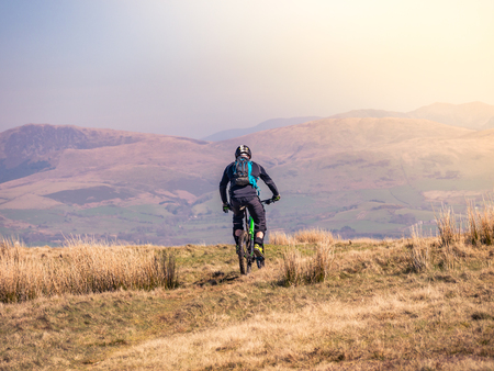 A mountain biker rides along top of Dent fell in the Lake district, Cumbria, England Editorial