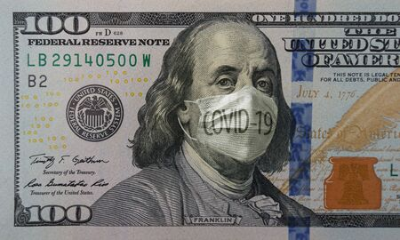Medical mask with COVID-19 inscription on a banknote of 100 dollars, concept of the global financial crisis. Face surgical mask on american money. Coronavirus in USA. Reklamní fotografie