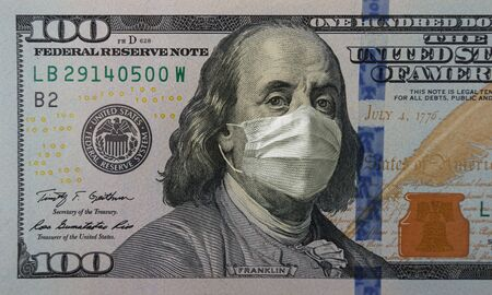 Medical mask on a banknote of 100 dollars, concept of the global financial crisis. Face surgical mask on american money. COVID-19 coronavirus in USA. Doctor mask protects against COVID-19. Reklamní fotografie