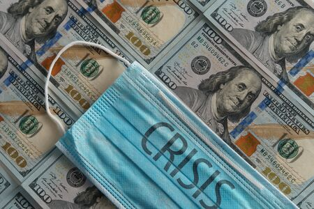 Medical face mask with crisis inscription on a one hundred dollar bills. American money. COVID-19 in USA. Coronavirus problems concept - medicine, financial crisis, economy problems Reklamní fotografie