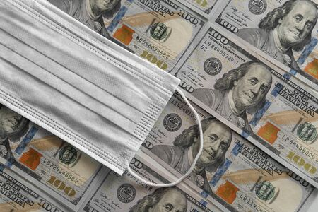 Medical face mask on one hundred dollar bill. American money. COVID-19 coronavirus in USA. Financial assistance for medicine concept
