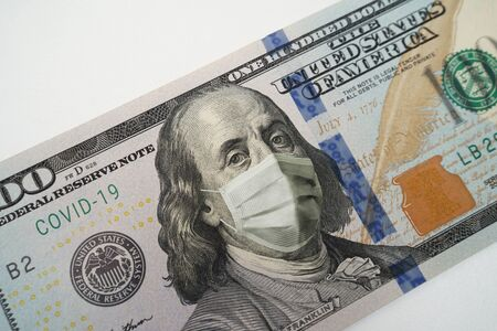 Medical mask on Franklins face on banknote of 100 dollars, concept of financial crisis. COVID-19 coronavirus in USA Reklamní fotografie