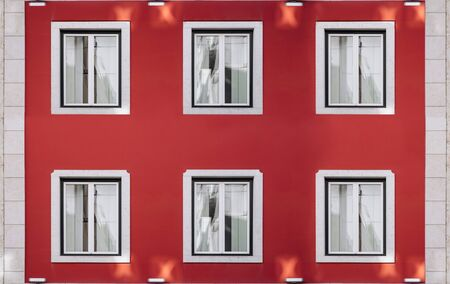 Six vintage windows on a bright red wall. Exterior facade of red historical house with apartments in Lisbon, Portugal. Urban vintage background Reklamní fotografie