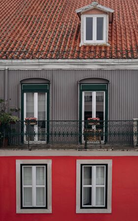 Facade of old colorful house with orange tiled roofs in Lisbon, Portugal. View on top of red grey color building with balcony and windows. Three levels Reklamní fotografie
