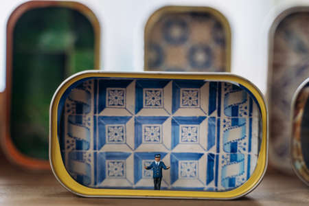 LISBON, PORTUGAL - JANUARY 2, 2020. Small figure of tram conductor in colorful tin of canned sardines in front of azulejo tiles wall background. Artwork in souvenir store in Lisbon, Portugal