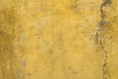 Yellow grunge cement painted cracked wall. Textured background