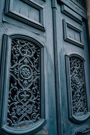Old vintage wooden rustic blue door. XIX century entrance to an old house. Detailed exterior vertical photo. Reklamní fotografie