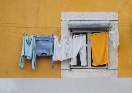 Line of clothes with blue blouse, white pants an yellow towel drying on ropes stretched outside colourful yellow facade with window in Lisbon, Portugal. Background