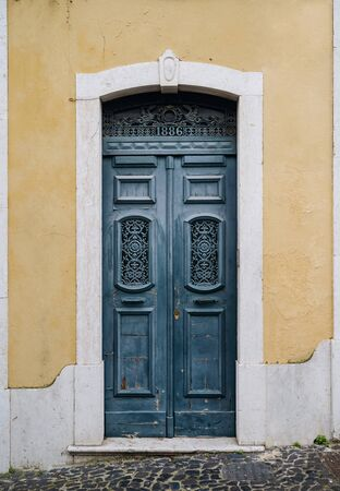 Old vintage wooden rustic blue door on a yellow wall. XIX century entrance to an old house. Detailed exterior vertical photo.