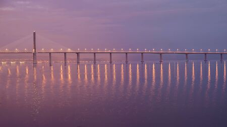 Vasco da Gama suspension bridge at in Lisbon, Portugal. Long exposure shoot. Dusk with red, pink blue sky and lantern reflections in water. Famous travel destination Reklamní fotografie
