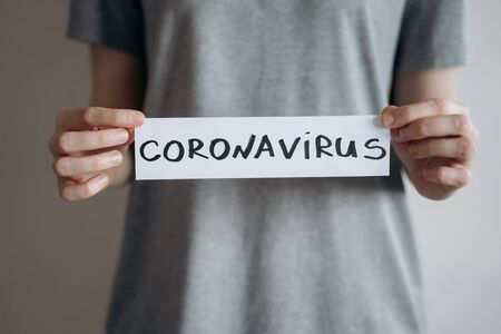 Woman in grey t-shirt holds sheet with the word Coronavirus. Pandemic of COVID-19. Coronavirus quarantine isolation concept. Stay at home. Close-up shot. Reklamní fotografie