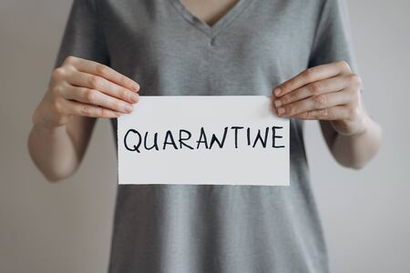 Woman in grey t-shirt holds sheet with the word Quarantine. Pandemic of COVID-19. Coronavirus quarantine isolation concept. Stay at home. Close-up shot.