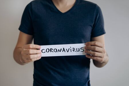 Man in blue t-shirt holds sheet with the word Coronavirus. Pandemic of COVID-19. Coronavirus quarantine isolation concept. Stay at home. Close-up shot.