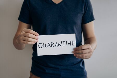 Man in blue t-shirt holds sheet with the word Quarantine. Pandemic of COVID-19. Coronavirus quarantine isolation concept. Stay at home. Close-up shot.