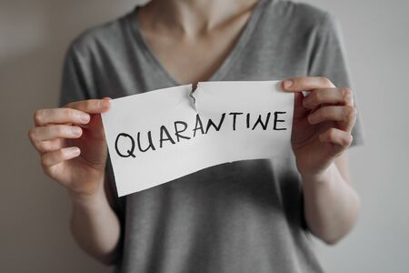 Victory against a coronavirus quarantine concept. Young woman in grey t-shirt tears the paper with the word Quarantine. Pandemic of COVID-19 is over. Finish of isolaion. Close up shot. Reklamní fotografie