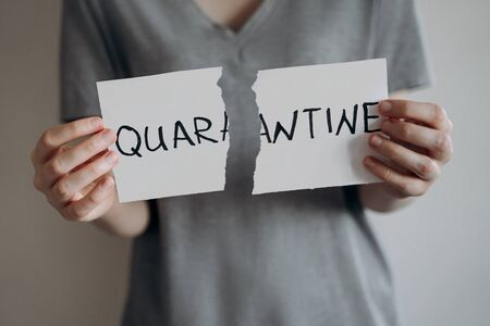 End of a coronavirus quarantine concept. Young woman in grey t-shirt tears the paper with the word Quarantine. Pandemic of COVID-19 is over. Finish of isolaion. Close up shot.