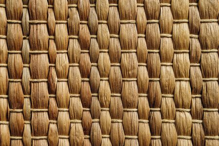 Handmade brown Wicker placemat made from water hyacinth. Top view, nature background, straw texture Reklamní fotografie