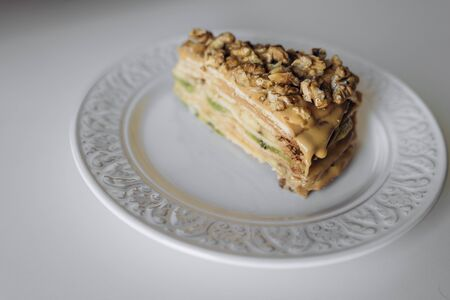 Piece of sweet homemade honey cake on plate with caramel and walnut nuts with kiwi and banana inside. Tasty brown cake dessert on white background