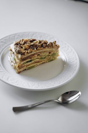 Piece of sweet homemade honey cake on plate with spoon with caramel and walnut nuts with kiwi and banana inside. Tasty brown cake dessert on white background