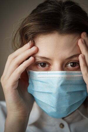 Young concerned and worried woman medical worker in protective medical face mask looking at camera. Doctor protection from Coronavirus, covid-19