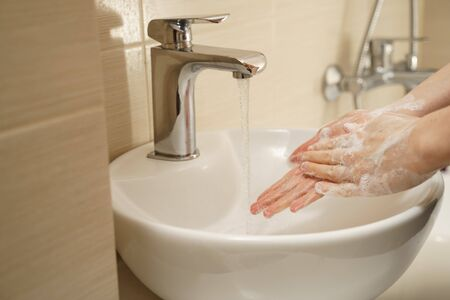 Washing hands with soap under running water. Protection against coronavirus